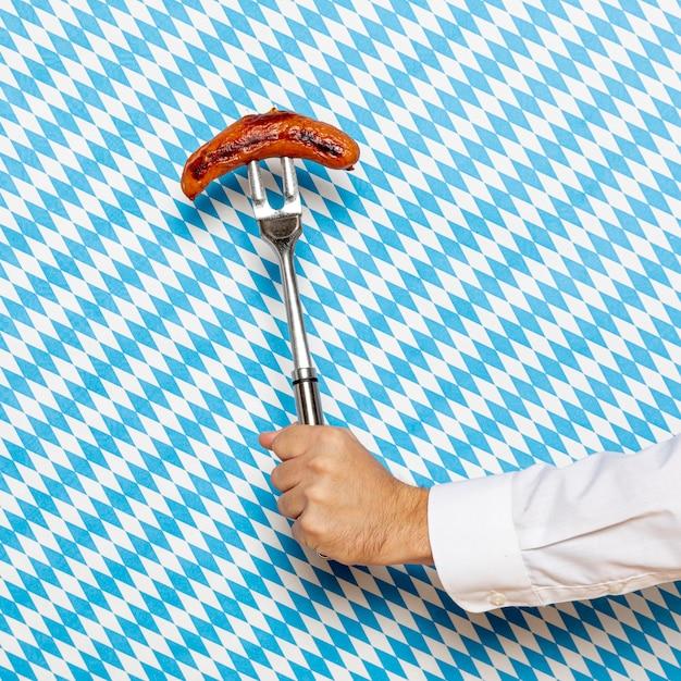Homme tenant des saucisses avec fond à motifs Photo gratuit