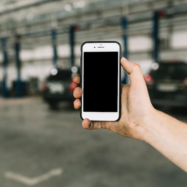 Homme tenant le smartphone au garage Photo gratuit