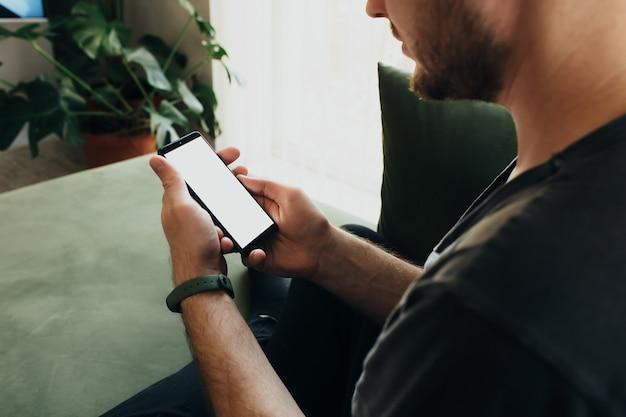 Homme Tenant Un Smartphone Avec écran Blanc Photo Premium