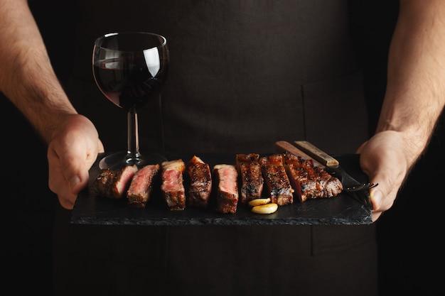 Homme tenant un steak de bœuf grillé juteux. Photo Premium
