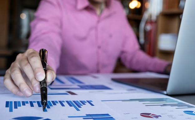 Homme tenant un stylo tout en travaillant avec un ordinateur portable Photo Premium