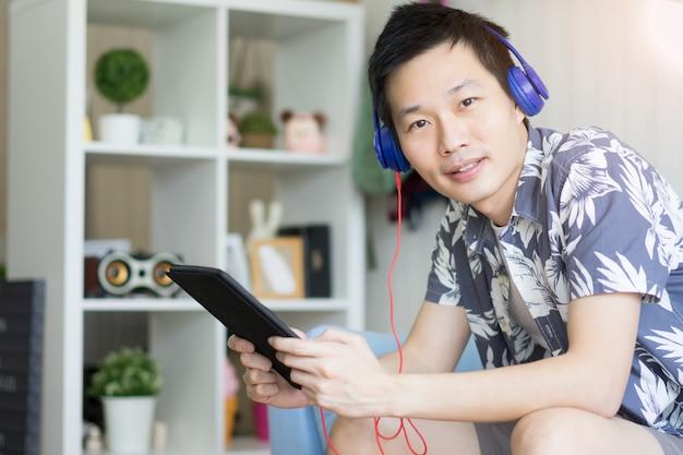 Un Homme Tenant Une Tablette Avec Des écouteurs Pour écouter De La Musique Dans Le Salon à La Maison. Photo Premium
