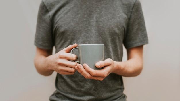 Homme Tenant Une Tasse à Café En Céramique Grise Photo gratuit