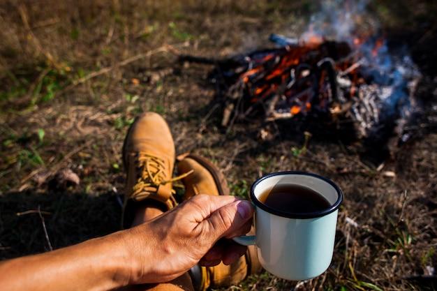 Homme tenant une tasse de café à côté d'un feu de camp Photo gratuit