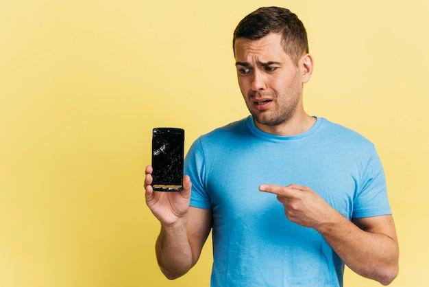 Homme Tenant Un Téléphone Cassé Photo gratuit