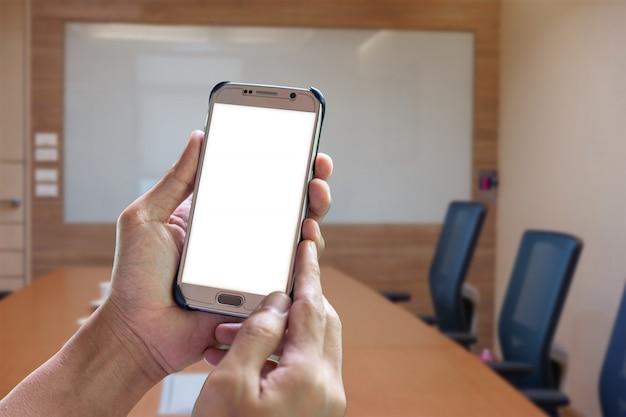 Homme tenant un téléphone intelligent à écran blanc dans la salle de réunion Photo Premium