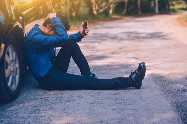 Homme tenant un téléphone intelligent mobile et la technologie en ligne internet pour faire du shopping avec les entreprises en voiture Photo Premium