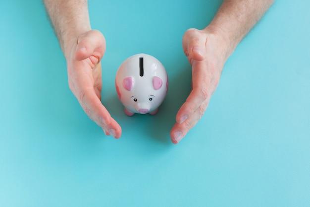 Homme tenant la tirelire sur fond bleu Photo Premium