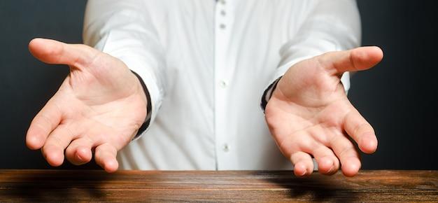 Un Homme Tend Ses Mains Dans Une Expression émotionnelle D'étonnement. Montrez La Cause Du Deuil Photo Premium
