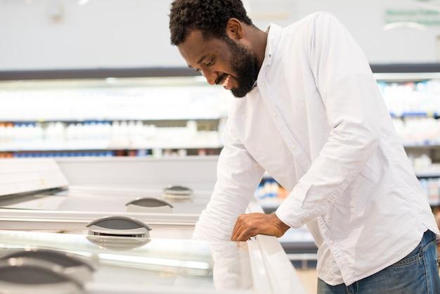 Homme tendre la main dans le congélateur du supermarché Photo gratuit