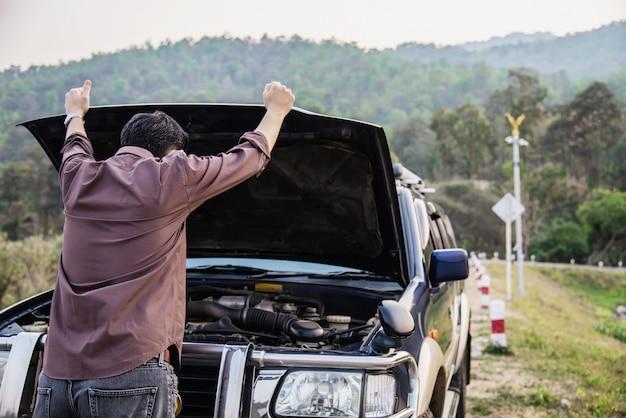 Un homme tente de résoudre un problème de moteur de voiture sur une route locale à chiang mai, en thaïlande Photo gratuit