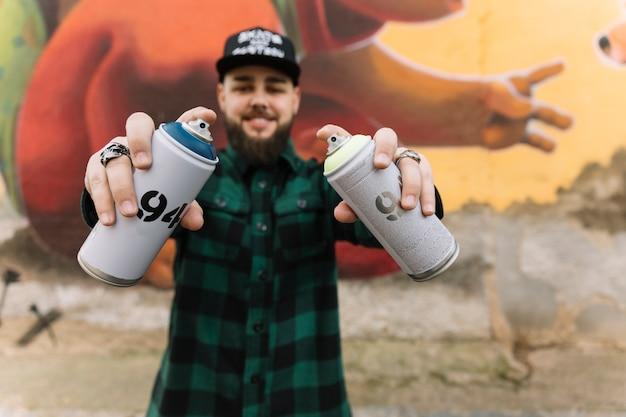 Homme, tenue, aérosols, à, mains, debout, contre, graffiti, mur Photo gratuit