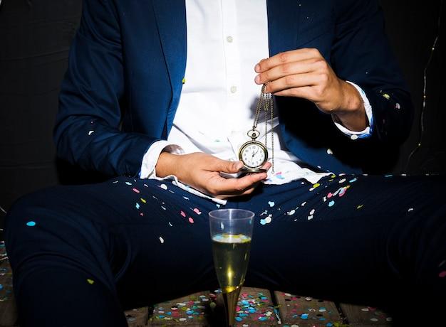 Homme en tenue de dîner, montre de poche près du verre entre les confettis Photo gratuit