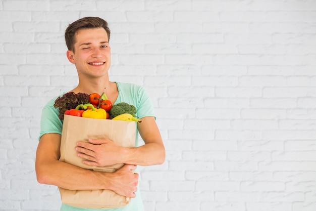 Homme, tenue, épicerie, sac, plein, fruits, végétal, clin d'oeil Photo gratuit