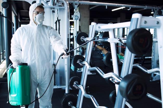 Homme En Tenue De Protection Blanche Désinfectant Et équipement De Fitness Et Poids Pour Arrêter La Propagation Du Virus Corona Très Contagieux Photo gratuit