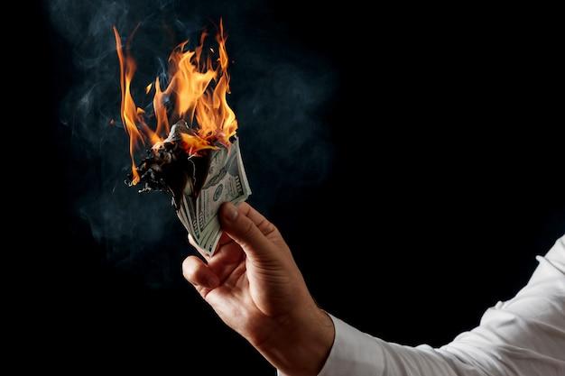 Un homme tient de l'argent en feu dans sa main Photo Premium