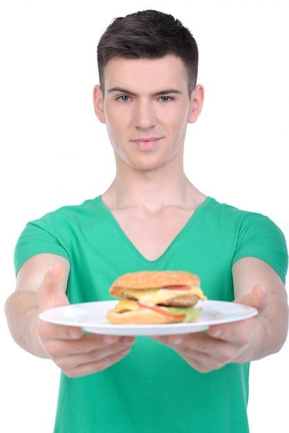 Un homme tient une assiette avec un hamburger dans ses mains et sourit. Photo Premium