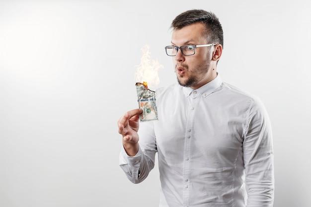 Un homme tient une facture d'argent en feu dans sa main Photo Premium
