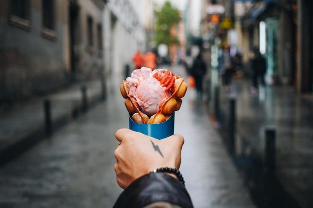 L'homme Tient La Gaufre à Bulles Du Camion De Nourriture De Rue Photo gratuit