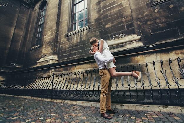 L'homme tient sa femme l'embrassant devant l'église Photo gratuit