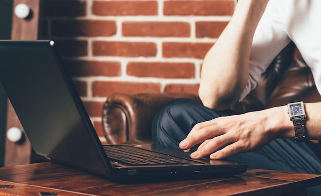 Un homme tient sa main sur le pavé tactile de l'ordinateur portable. il est assis sur un fauteuil marron dans son propre cabinet Photo Premium