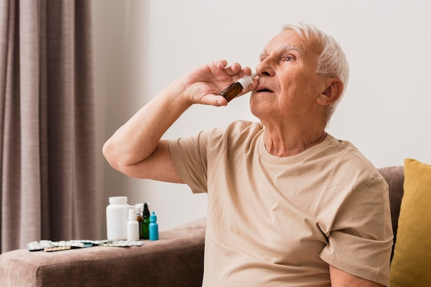 Homme De Tir Moyen à L'aide D'un Spray Nasal Photo gratuit