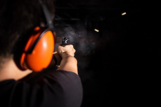 Un homme tire un pistolet, une balle de feu et un couvre-oreille orange dans le champ de tir Photo Premium