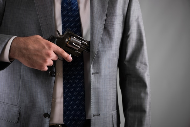 Un homme tire son arme de sa poche Photo Premium