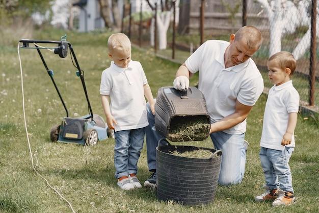 Homme De Tondeuse à Gazon Travaillant Sur L'arrière-cour Avec Fils Photo gratuit