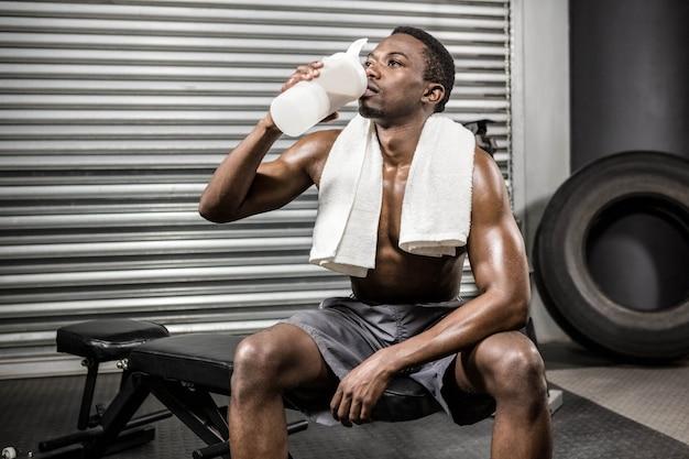 Homme torse nu, buvant une boisson protéinée au gymnase de crossfit Photo Premium