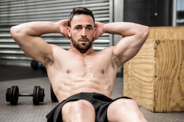 Homme torse nu faisant des abdominaux crunch au gymnase de crossfit Photo Premium