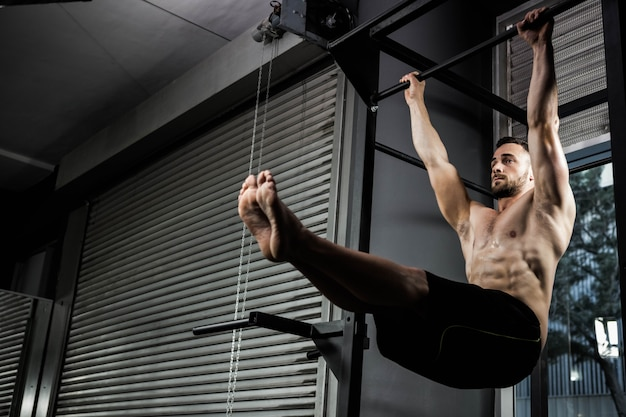 Homme torse nu faisant pull up au gymnase de crossfit Photo Premium