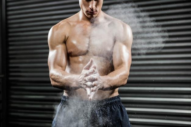 Homme torse nu en frappant des mains avec du talc à la salle de gym crossfit Photo Premium