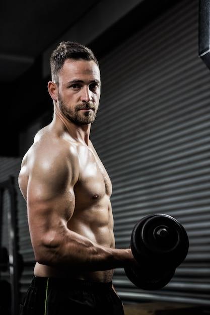 Homme torse nu, soulevant un haltère lourd au gymnase de crossfit Photo Premium