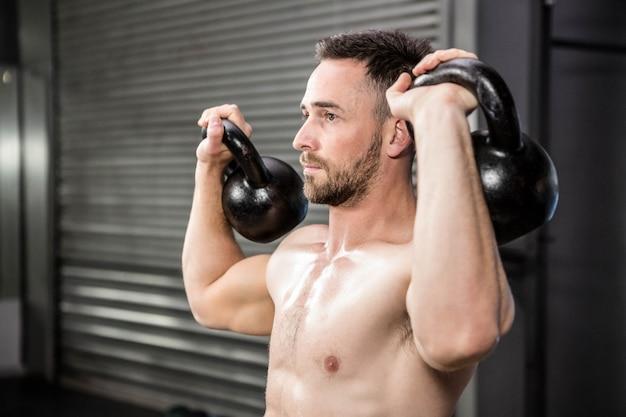 Homme torse nu, soulevant des kettlebells au gymnase de crossfit Photo Premium