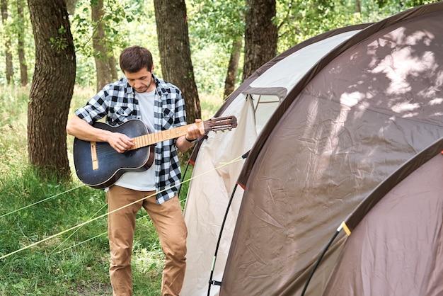 Homme De Touriste Avec Guitare Près D'une Tente De Camping Photo Premium