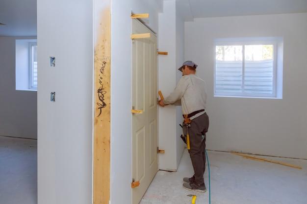 Homme à tout faire installer la nouvelle porte jumelle dans la chambre Photo Premium
