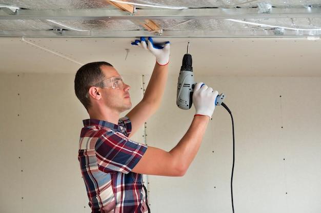 Homme en train de fixer un plafond suspendu en placoplâtre Photo Premium