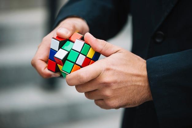 Homme en train de résoudre le cube de rubik Photo gratuit