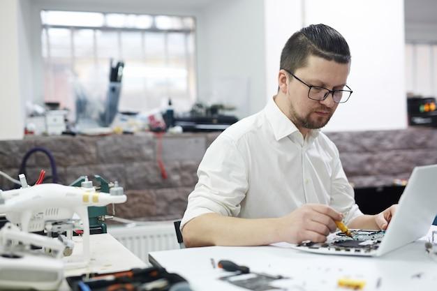 Homme travaillant avec l'électronique Photo gratuit