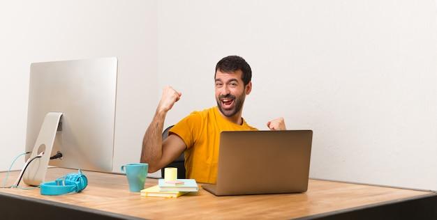 Homme travaillant avec laptot dans un bureau célébrant une victoire Photo Premium