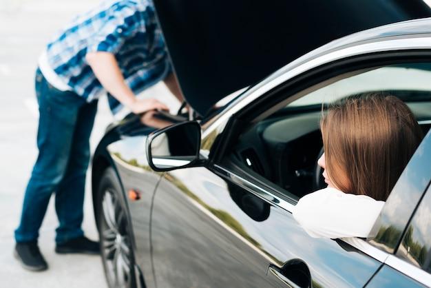 Homme travaillant sur un moteur et une femme assise dans une voiture Photo gratuit
