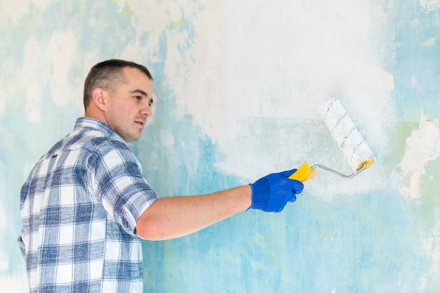 Homme Travaillant Sur Un Mur Avec Un Rouleau à Peinture Photo gratuit