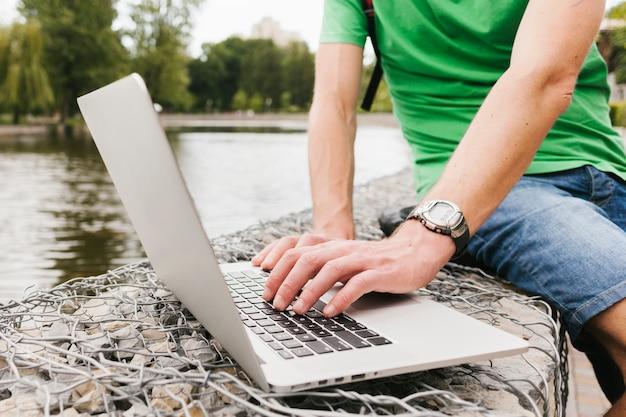 Homme travaillant sur l'ordinateur portable au bord du lac Photo gratuit