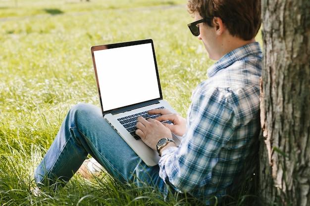 Homme Travaillant Sur L'ordinateur Portable Dans Le Parc Photo gratuit