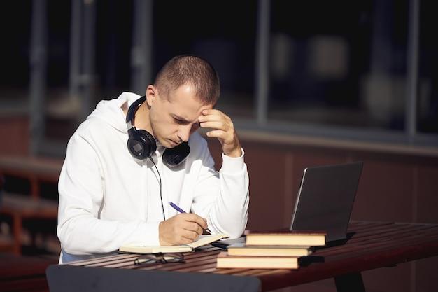 Homme Travaillant Sur Un Ordinateur Portable Et écrivant Dans Un Ordinateur Portable Assis Dans La Rue à Une Table. Distanciation Sociale Pendant Le Coronavirus Photo Premium