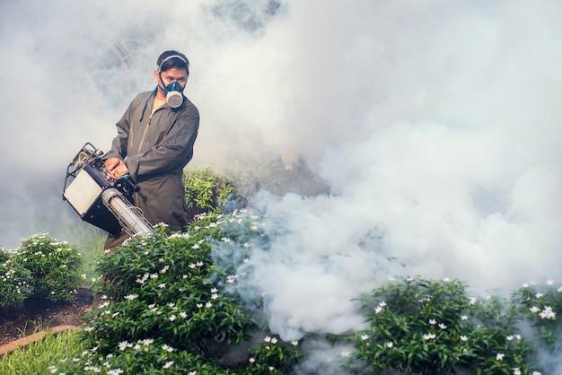 L'homme Travaille à La Buée Pour éliminer Les Moustiques Photo Premium