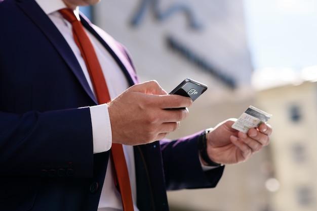 L'homme travaille avec une carte de crédit et un téléphone. Photo Premium