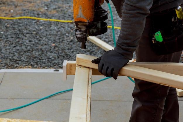 Un homme travaille à la construction d'un mur de maison. il est sur une échelle de tir cadré horizontalement. Photo Premium