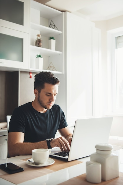 L'homme Travaille à Distance De La Maison à L'aide D'un Ordinateur Portable Photo Premium